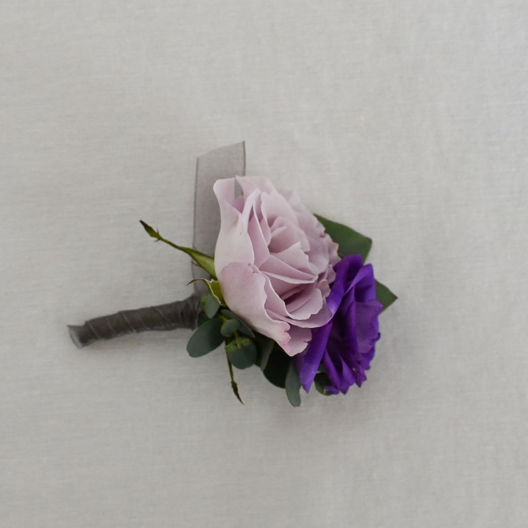 Red Fox Floral Purple Boutonniere. A boutonniere made with a dark purple flower, lavender and white accents and a mix of green foliage.