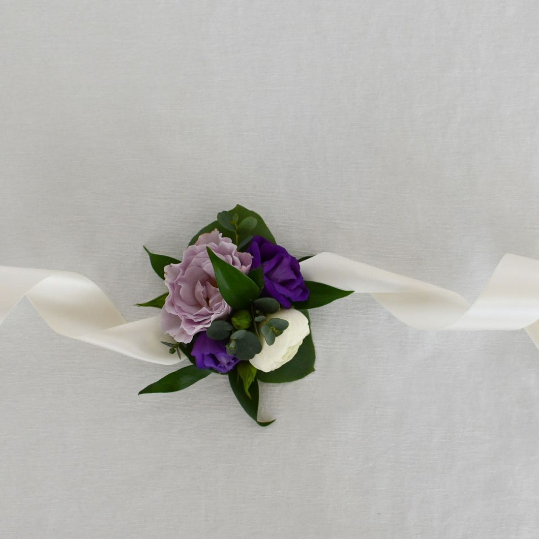 Red Fox Floral Purple Corsage. A wrist corsage made with purple and lavender flowers with white accents and greens tied with white satin ribbon.