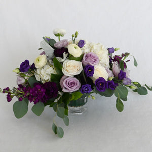 Red Fox Floral Large Purple Centerpiece. A luxurious arrangement with picked from the garden texture made with a mix of purples lavender, and whites. Includes garden roses, spray roses, ranunculus, lisianthus, stock with eucalyptus and green foliage.
