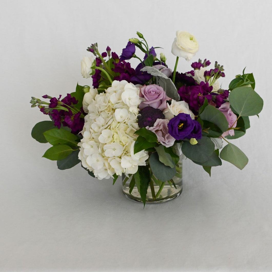 Red Fox Floral Small Purple Centerpiece. An organically designed arrangement made with a mix of purples, lavender and whites. Includes garden roses, spray roses, ranunculus, lisianthus, carnations, stock with eucalyptus and green foliage.