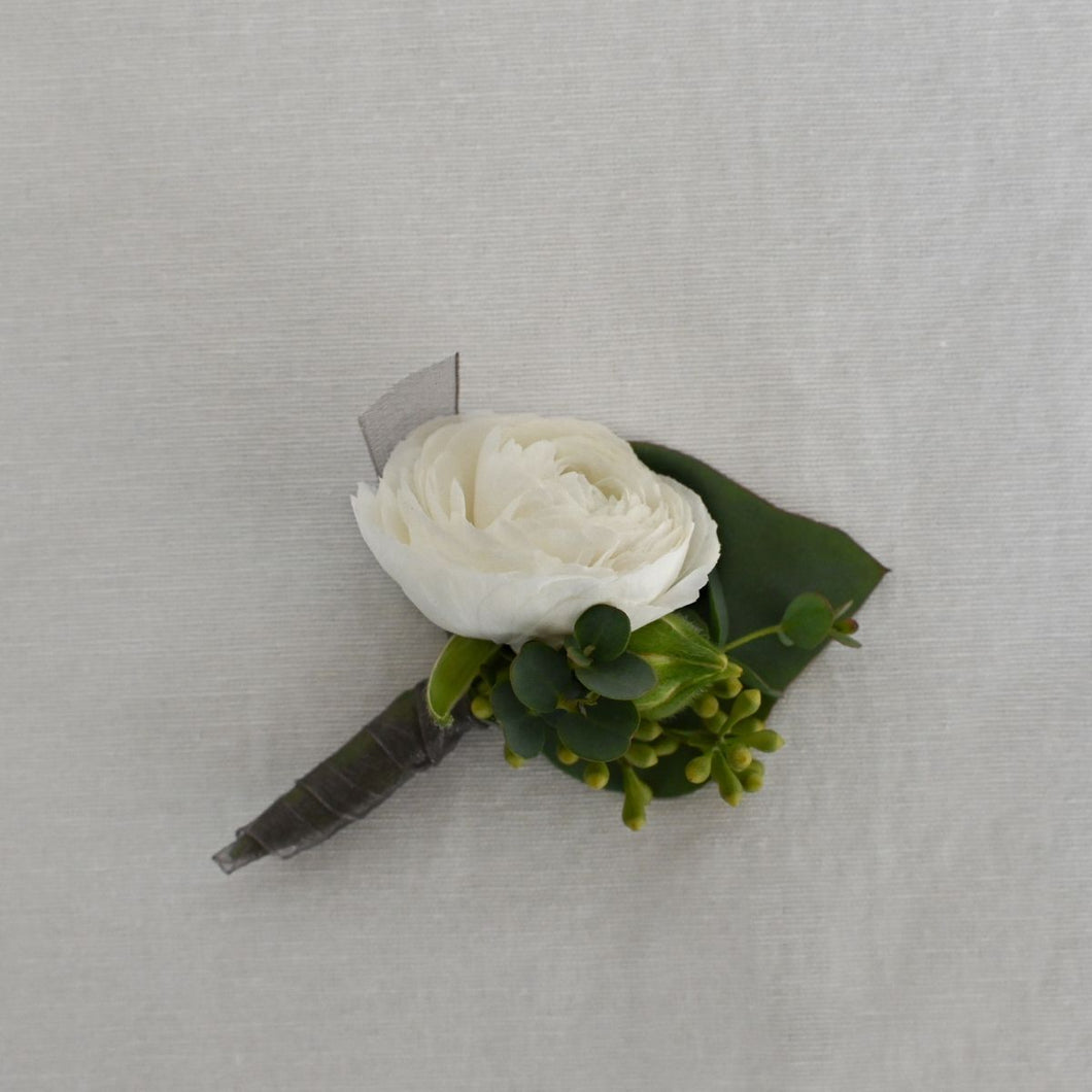 Red Fox Floral Romantic Garden Boutonniere. A boutonniere made with a white flower, accents, and a mix of green foliage.  Stems will be wrapped in gray ribbon.