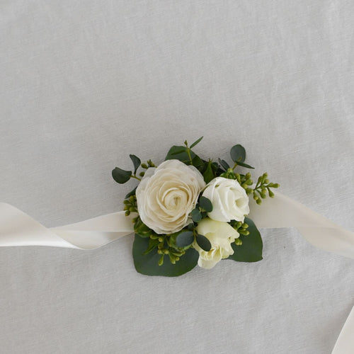 Red Fox Floral Romantic Garden Corsage. A wrist corsage made with white flowers and accent greens tied with white satin ribbon.