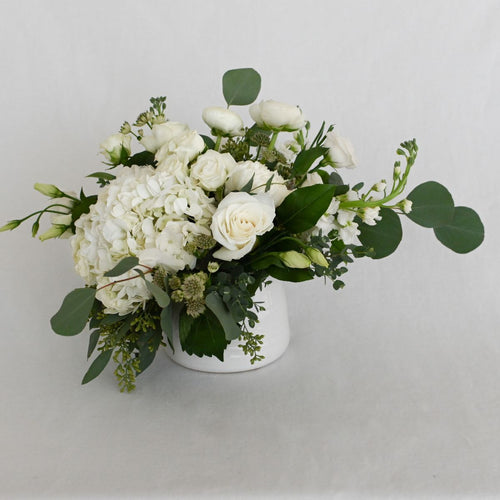 Red Fox Floral Small Romantic Garden Centerpiece. A low and lush arrangement with picked from the garden texture made with white garden roses, spray roses, football mums, ranunculus, lisianthus, white accents and eucalyptus and green foliage.