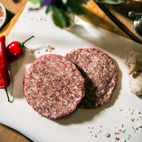 Two organic grass-fed beef burgers displayed on a chopping board, at the Goodwood Farm Shop, with red peppers and garlic cloves.