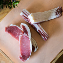 Load image into Gallery viewer, Four sets of Goodwood's organic back bacon rashers, displayed on a chopping board at Goodwood Farm Shop.