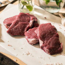 Load image into Gallery viewer, Close up of four organic grass-fed lamb leg steaks on a chopping board at the Goodwood Farm Shop.