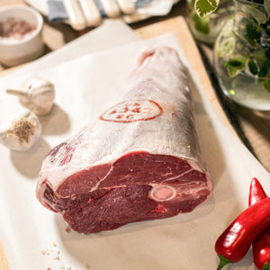 A roasting joint of organic grass-fed leg of lamb on the bone placed on a chopping board, at the Goodwood Farm Shop, with red peppers and garlic cloves.