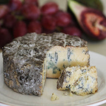 Load image into Gallery viewer, Goodwood's Molecomb Blue soft blue veined cheese, with a dark smoky grey crust, displayed as part of a cheese board.