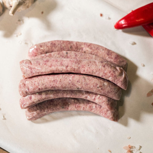 Grass-fed organic chipolata pork sausages shown on a chopping board at Goodwood Farm Shop.