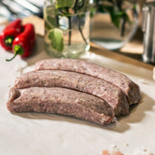 Load image into Gallery viewer, Three Goodwood organic Cumberland pork sausages on a chopping board at Goodwood Farm Shop.