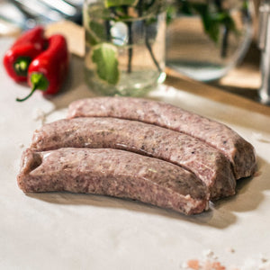 Three Goodwood organic Cumberland pork sausages on a chopping board at Goodwood Farm Shop.