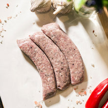 Load image into Gallery viewer, Three Goodwood organic pork sausages on a chopping board at Goodwood Farm Shop.