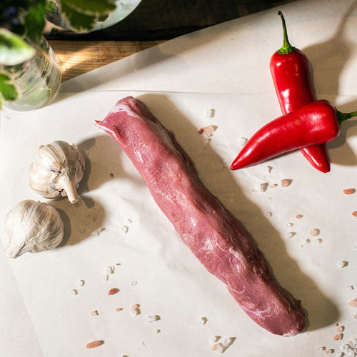 Goodwood's organic grass-fed pork tenderloin, displayed on a chopping board with garlic cloves and red peppers.