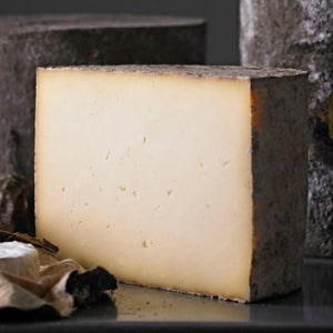 Goodwood's Charlton farmhouse cheese ready to be sliced for a cheese board, available at Goodwood Farm Shop.
