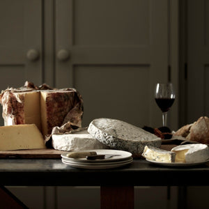 A cheese board selection of handmade Goodwood Farm Shop cheeses, displayed on a table.