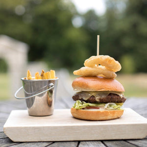 Dining outdoors at The Kennels with an organic beef burger served in a bun with cheese, lettuce and tomato with sides of chips and onion rings.