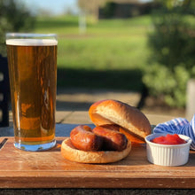 Load image into Gallery viewer, Goodwood's organic pork sausage recipe, used in a bap with tomato ketchup served alongside a beer at the Goodwood Bar and Grill restaurant.