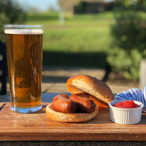 Goodwood's organic pork sausage recipe, used in a bap with tomato ketchup served alongside a beer at the Goodwood Bar and Grill restaurant.