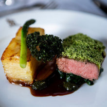 Load image into Gallery viewer, A plate of organic lamb leg steak with a seasoned crust, served at a Goodwood House wedding breakfast.
