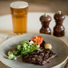 Load image into Gallery viewer, An organic beef rump steak served on a plate, alongside a beer, at the Goodwood Bar and Grill restaurant.