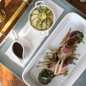 An organic lamb butcher's board containing racks of lamb, a potato hot pot and gravy - a recipe served at Goodwood's sustainable flagship restaurant Farmer, Butcher, Chef.
