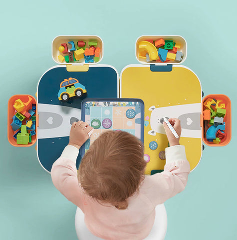 child writing at activty table with Duplo blocks in storage holders