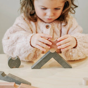 girl playing with wooden balancing blocks puzzle shapes