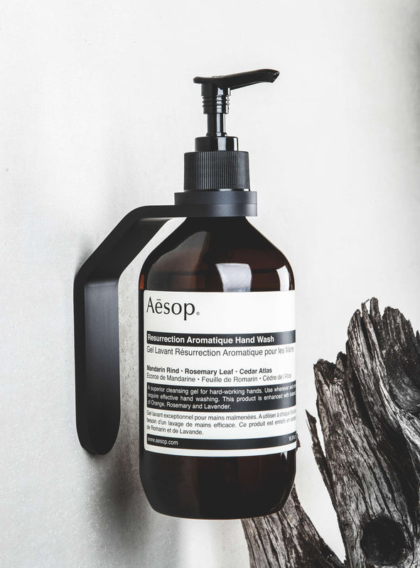 black wall mount with black spacer ring holding AESOP Resurrection Aromatique Hand Wash on white wall with black wood in background