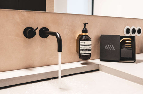 AESOP Resurrection Aromatique Hand Wash on beige tadelakt bathroom faucet with black vola water tap in brass mount