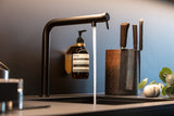 brass wall mount with brass spacer ring holding AESOP Resurrection Aromatique Hand Wash on black vola kitchen faucet next to knife block and running water