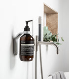 palladium wall mount with palladium spacer ring holding AESOP Equalising Shampoo in white luxury bathroom next to bathtub with flower and vase in background