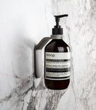 palladium wall mount with palladium spacer ring holding AESOP Geranium Leaf Body Cleanser on natural marble stone