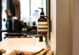 black wall mount with light grey spacer ring holding AESOP Resurrection Aromatique Hand Wash on beige wall in business shop next to black faucet