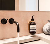 brass wall mount with brass spacer ring holding AESOP Resurrection Aromatique Hand Wash on tadelakt beige wall next to black vola water tap and white grey vase