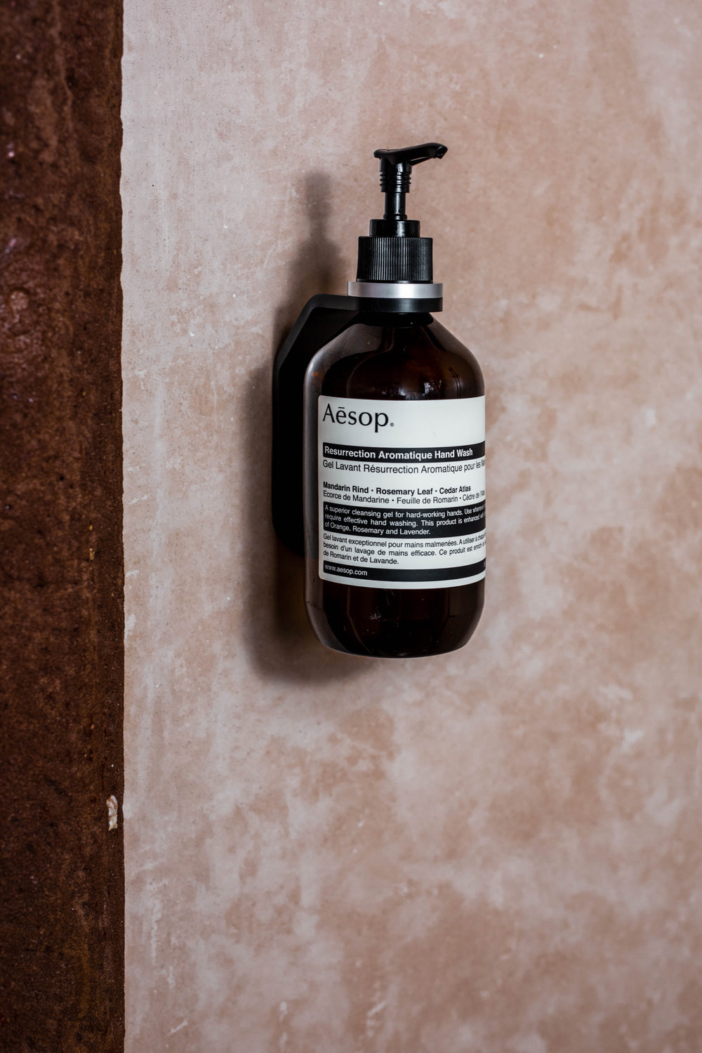 black wall mount with light grey spacer ring holding AESOP Resurrection Aromatique Hand Wash on tadelakt wall in beautiful shower