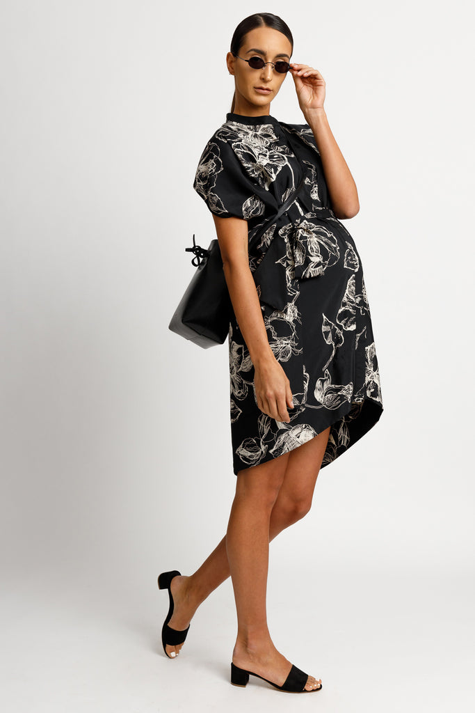 FORMERLY YAN Maternity Figure Flattering Button Down Shirt Dress with Cap Sleeves and Self Tie. Knee Length. Black Floral Print. Adjustable to Wear During and After Pregnancy. Nursing Friendly