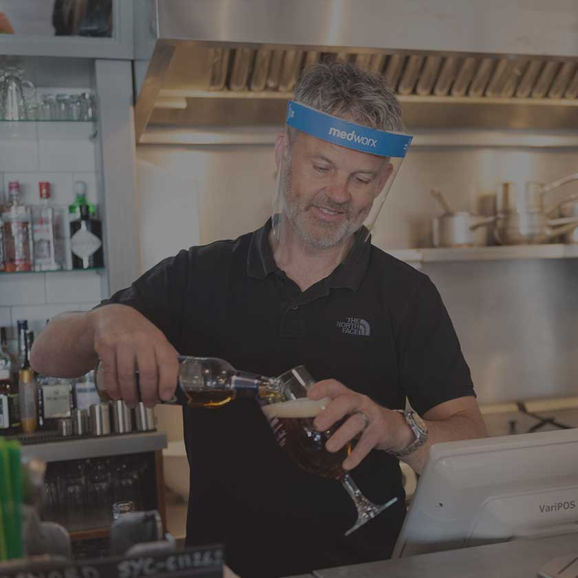 Man in black polo shirt working behind a bar wearing a Medworx Face Shield with blue strip.