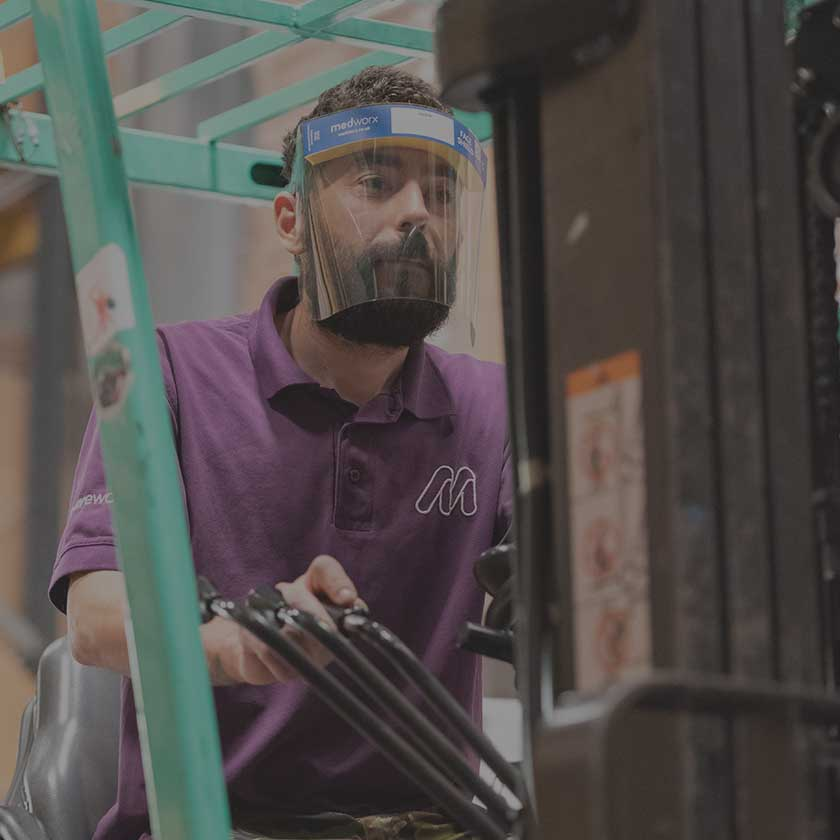 Man operating a forklift truck in warehouse wearing a Medworx Face Shield.