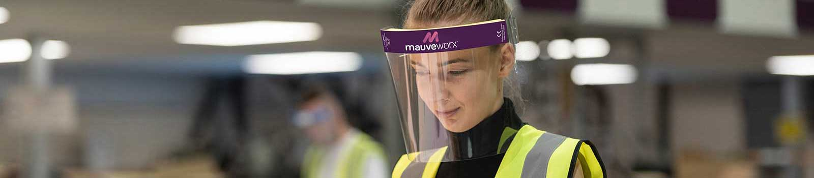Key worker using custom branded face shield in factory wearing high vis jacket