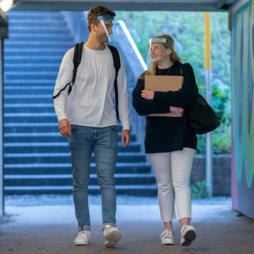 Male and female students chatting whilst wearing Medworx face shields with customisable stickers to match outfits.