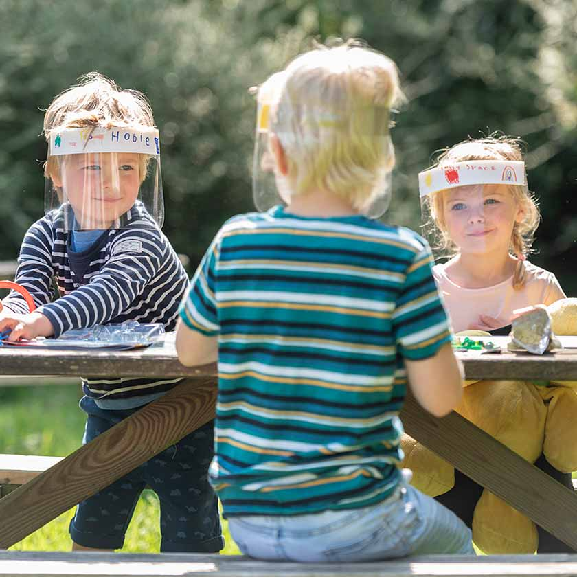 Three young children playing on a bench together wearing the children's face shield which they have drawn on to customise.
