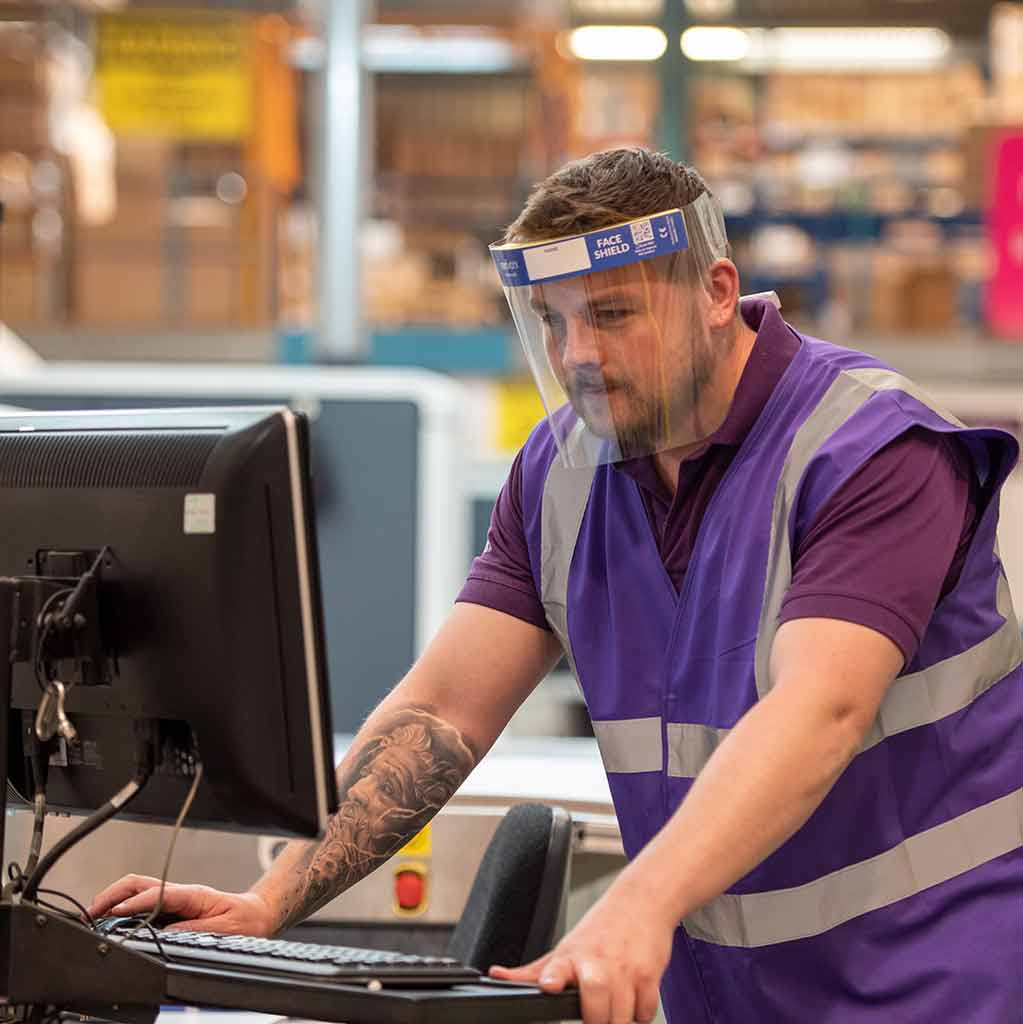 Man with a tattoo on arm working on a computer in a warehouse wearing a purple hi vis jacket and Medworx face shield.