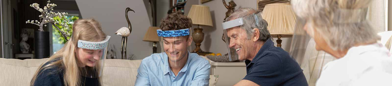 Family of four chatting in a living room wearing the Medworx face visors with a variety of patterned stickers.