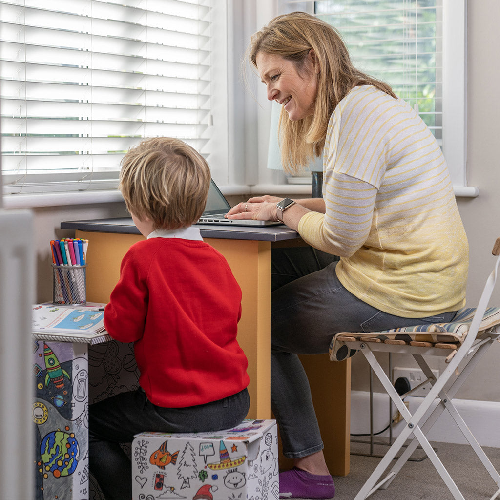 A mum sits working at her yellow Pack a Desk whilst talking to her son who is sat next to her at his Pack a Desk Junior.
