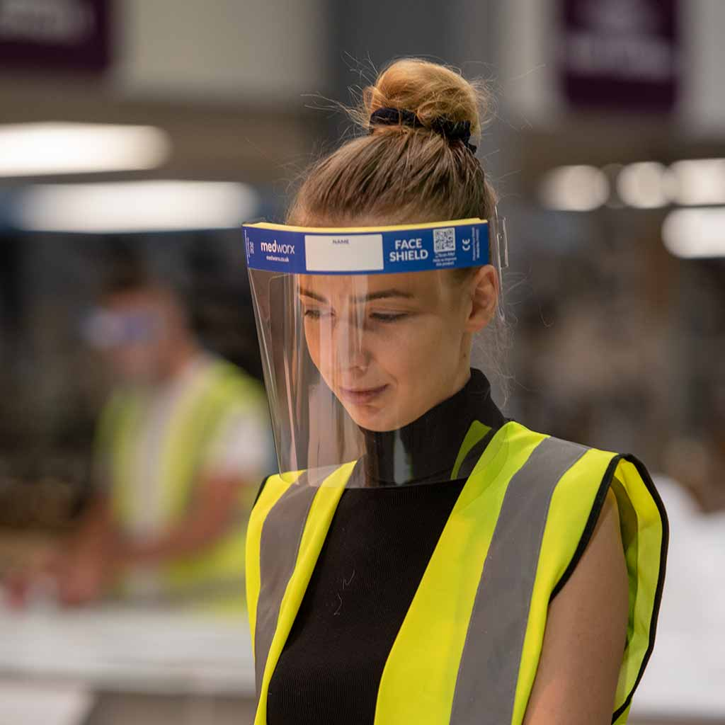 Women wearing a yellow hi vis jacket in a warehouse wearing the Medworx face shield.