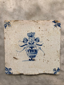 17th century delft tile with flowervase
