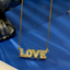 The word LOVE, in all uppercase gold letters, studded with clear crystals, suspended from a gold chain