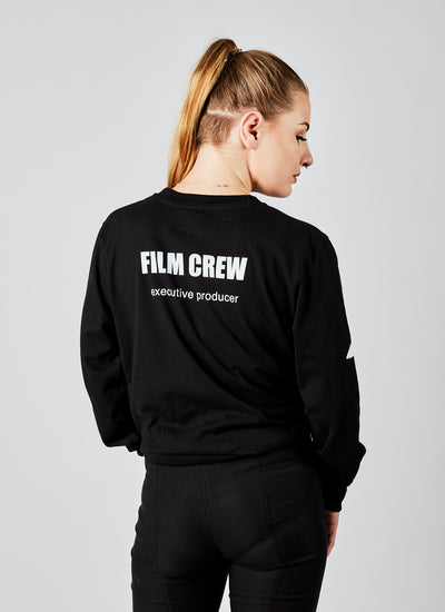 "Back of a woman wearing a black, long-sleeved ""Executive Producer"" film crew shirt from Melbourne video production company, Enamoured Iris."