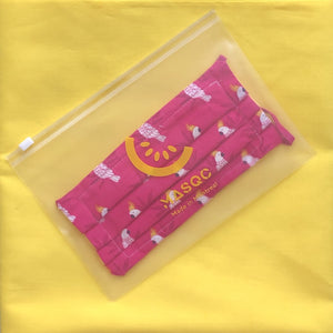 Frosted biodegradable PVC pouch containing a fuschia artisanal mask on yellow background. done by www.masqc.org