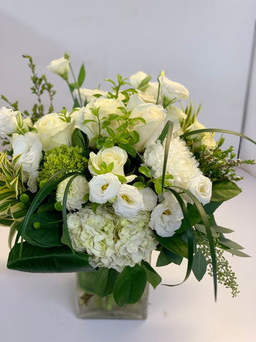 sympathy flower arrangement in a glass vase with white Dahlias Lisianthus hydrangeas commercial mums song of India lily grass roses